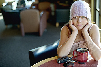 Teenage girl (15-17) with cell phone and coffee cup, sitting in cafe