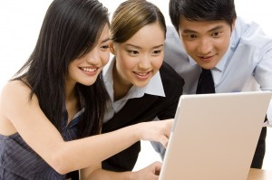Group of three pretty young Asian people looking eagerly at a computer scree (reading a blog or social media site)..